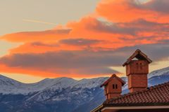 Two chimneys of a house on the background of a sunset. The profiles of two chimneys drawn against the background of a mountain at sunset Royalty Free Stock Images