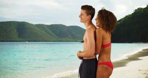 Profilez la vue des couples se tenant sur la plage dans les Caraïbe Photographie stock
