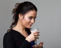 Profilez le portrait d'une brune attrayante gardant un verre de m Image libre de droits