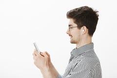 Profilez le portrait du modèle masculin attrayant insouciant joyeux dans les verres et la chemise rayée, tenant le smartphone tan Photo stock