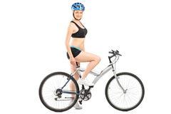 Profilez le tir d'un cycliste féminin s'asseyant sur un vélo Image stock