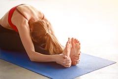 Profilez le tir de la jeune femme s'étendant pour toucher ses orteils tout en se reposant sur le fond blanc Photographie stock
