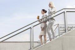 Profilez le tir des femmes d'affaires abaissant des escaliers contre le ciel Photographie stock libre de droits