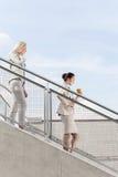 Profilez le tir des femmes d'affaires abaissant des escaliers ensemble contre le ciel Image libre de droits