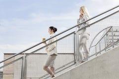 Profilez le tir des femmes d'affaires tenant la tasse et le téléphone portable jetables tout en abaissant des escaliers ensemble c Photos libres de droits