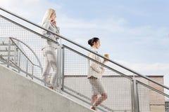 Profilez le tir des femmes d'affaires tenant la tasse et le téléphone portable jetables tout en abaissant des escaliers ensemble  Photographie stock libre de droits
