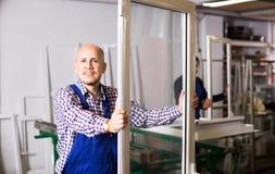 Profili e finestre del PVC dei prodotti degli operai fotografia stock libera da diritti