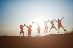 Profili i bambini che giocano sul tempo felice del tramonto dell'estate fotografia stock libera da diritti