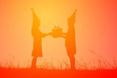 Profili i bambini che tengono il contenitore di regalo sul tramonto del cielo, concetto Immagini Stock