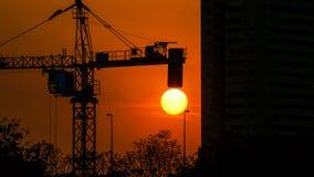 Profili il cantiere di crepuscolo della gru sopra il fondo del tramonto Immagine Stock
