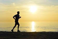Profili il giovane uomo di sport che corre all'aperto sulla spiaggia al tramonto con il cielo arancio fotografie stock