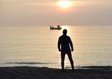 Profili il giovane uomo di sport che osserva all'oceano dopo l'allenamento corrente della spiaggia il tramonto fotografia stock