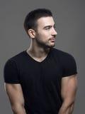 Profili il punto di vista dell'uomo adatto dei giovani sicuri felici nel distogliere lo sguardo nero in bianco della camicia immagini stock