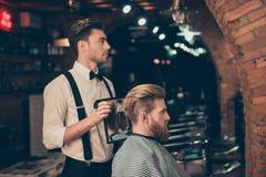 Profili il punto di vista dello stilista vestito di classe bello del negozio di barbiere, che fotografia stock