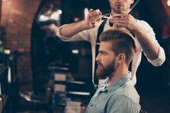Profili il punto di vista di un cliente alla moda barbuto rosso del negozio di barbiere È fotografia stock