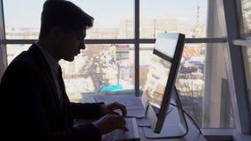 Profili il ritratto dell'uomo d'affari, che sta lavorando al computer nell'ufficio con la visualizzazione piacevole della città n stock footage