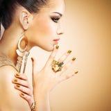 Profili il ritratto della donna di modo con bella mani dorata immagine stock