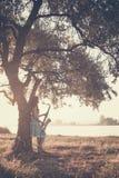 Profili il ritratto di bella giovane donna vicino al tronco di un albero in natura con il sax Immagine Stock