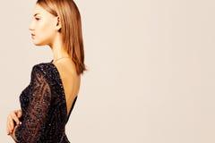 Profili il ritratto di una ragazza elegante che porta un vestito con ampia scollatura sulla schiena I Immagini Stock