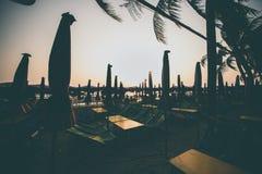 Profili il tramonto della sedia di spiaggia sulla spiaggia fotografia stock libera da diritti