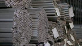 Profili il tubo in un magazzino coperto, tubo di profilo risieduto nelle file in un grande magazzino, magazzino con metallo video d archivio
