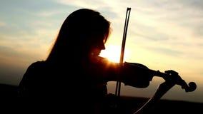Profili il violinista della ragazza che gioca il violino al fondo del cielo del tramonto stock footage