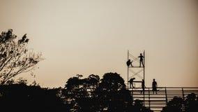 Profili l'immagine di un gruppo di lavoratori che lavorano all'armatura per costruzione Immagine Stock Libera da Diritti