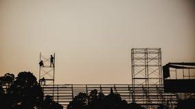Profili l'immagine di un gruppo di lavoratori che lavorano all'armatura per costruzione Immagini Stock