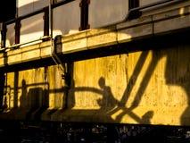 Profili l'ombra dell'uomo che va su sulla scala mobile Fotografie Stock