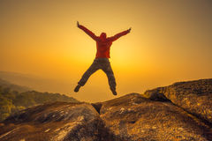 Profili l'uomo che salta nel cielo del tramonto Fotografia Stock