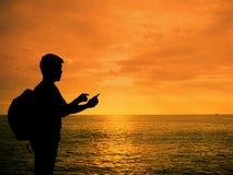 Profili l'uomo con lo smartphone in mani al tramonto Fotografia Stock Libera da Diritti