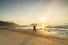 Profili l'uomo ed il tramonto sulle feste di vacanza della spiaggia con la e Immagini Stock