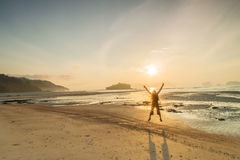 Profili l'uomo ed il tramonto sulle feste di vacanza della spiaggia con la e Immagine Stock