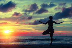 Profili l'yoga di pratica della giovane donna sulla spiaggia al tramonto immagine stock