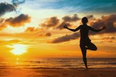 Profili l'yoga di pratica della giovane donna sulla spiaggia al tramonto distendasi Fotografia Stock