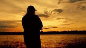 Profili la canna da pesca di lancio del pescatore in fiume sul tramonto di sera del fondo Bello tramonto di sera durante la pesca archivi video