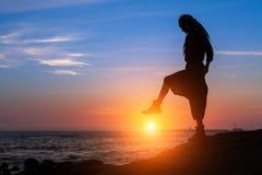Profili la donna che posa sulla riva di mare durante il tramonto stupefacente immagine stock