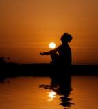 Profili la donna che si siede e che si rilassa sul tramonto arancio Fotografie Stock Libere da Diritti
