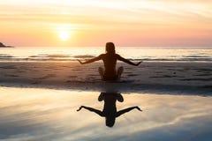 Profili la donna di yoga sui precedenti del mare e del tramonto stupefacente Immagine Stock Libera da Diritti
