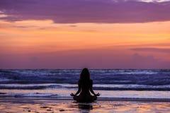 Profili la giovane donna che fa l'yoga sulla spiaggia al tramonto immagine stock libera da diritti