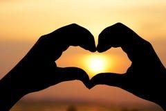 Profili la mano nella forma del cuore con l'alba nel mezzo e nella spiaggia come concetto del biglietto di S. Valentino del fondo Fotografia Stock