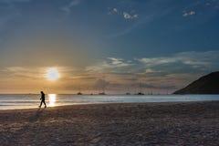 Profili la passeggiata dell'uomo, il tramonto in mare sulla spiaggia Immagini Stock