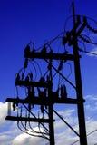 Profili la posta dell'elettricità con il fondo del cielo blu e metallico Fotografia Stock