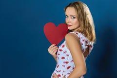 Profili la ragazza abbastanza bionda che tiene il cuore di carta rosso Fotografia Stock