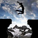Profili la ragazza che salta sopra la lacuna Fotografie Stock Libere da Diritti