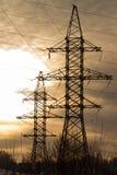 Profili la torre elettrica ad alta tensione su tempo del tramonto ed il cielo sul fondo di tempo del tramonto Fotografie Stock
