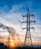 Profili la torre elettrica ad alta tensione su tempo del tramonto ed il cielo sul fondo di tempo del tramonto Fotografie Stock Libere da Diritti