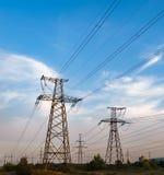Profili la torre elettrica ad alta tensione su tempo del tramonto ed il cielo sul fondo di tempo del tramonto Immagini Stock