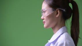 Profili la vista dei vetri di protezione d'uso di giovane bello medico asiatico della donna stock footage
