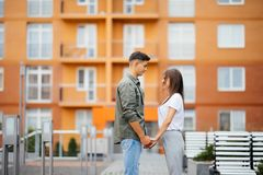 Profili la vista di giovane coppia attraente che se tiene per mano e che esamina immagine stock